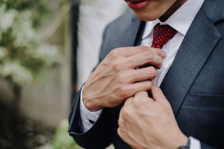 Midsection of businessman wearing suit outdoors
