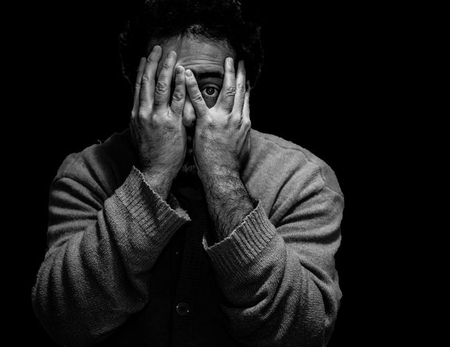 Portrait of man with hands covering face against black background