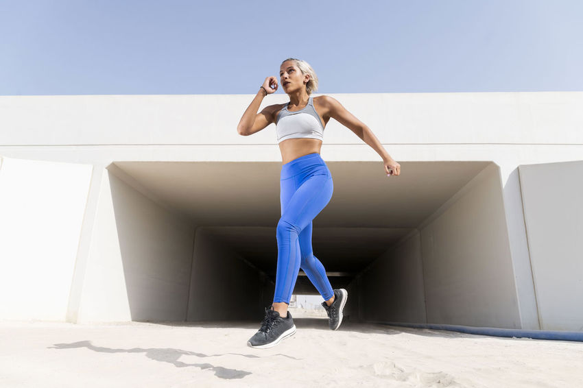 Middle Eastern Girl with short braided hair exercising in a urban setting with a tunnel in the back ground wearing blue and gray fitness outfit on a hot bright sunny day. Exercising Jumping Off Rocks Sitting Adult Architecture Beautiful Woman Bright Day Day Dusty Fitness Model Front View Full Length Hairstyle Hot Day ☀ Leisure Activity Lifestyles Middle Eastern Woman Nature One Person Outdoors Real People Shadow Sky Sport Sports Clothing Stretching Sunlight Women Young Adult Young Women