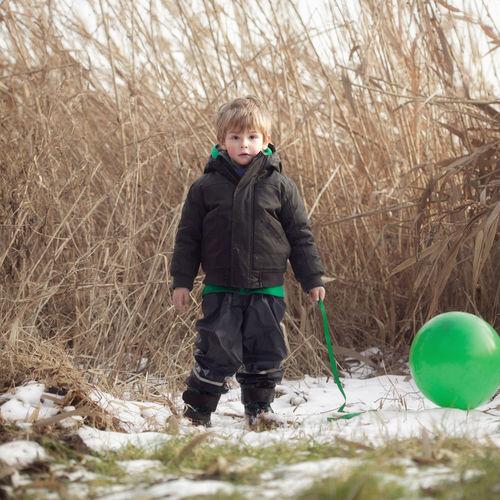 Full length portrait of smiling boy standing in snow