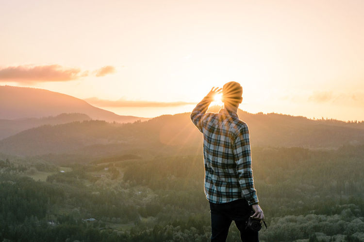 Rear View Of Man Looking At View While Standing On Mountain Against Sky During Sunset