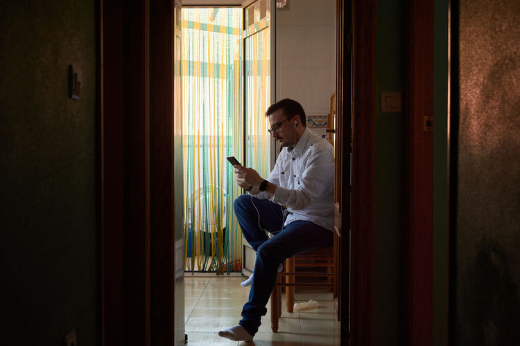 Young man using mobile phone while sitting on door