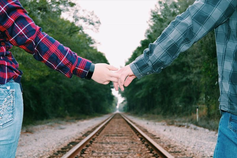Midsection of couple with holding hands over railroad track against trees