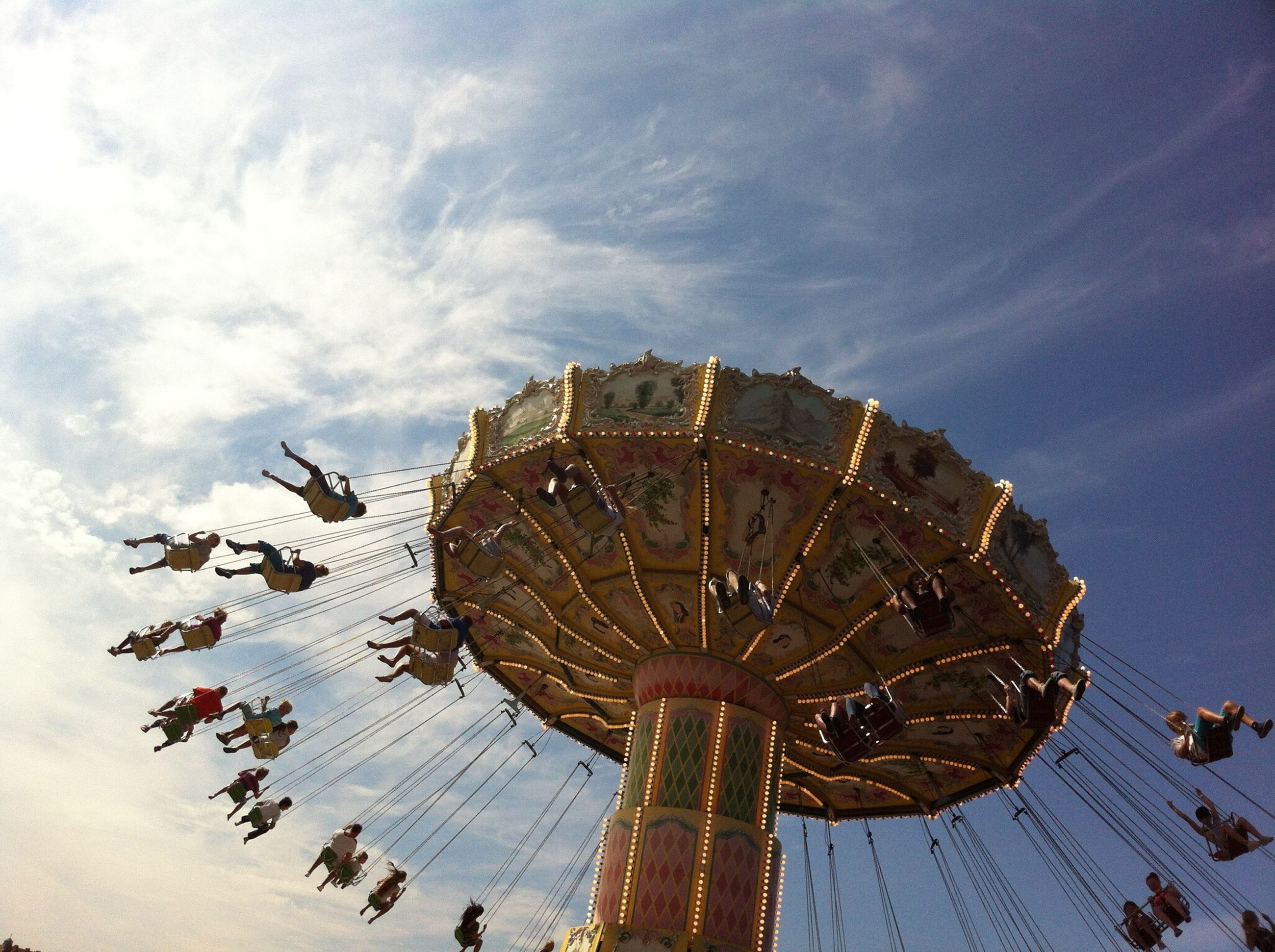 amusement park, sky, arts culture and entertainment, low angle view, leisure activity, amusement park ride, ferris wheel, outdoors, cloud - sky, no people, chain swing ride, day