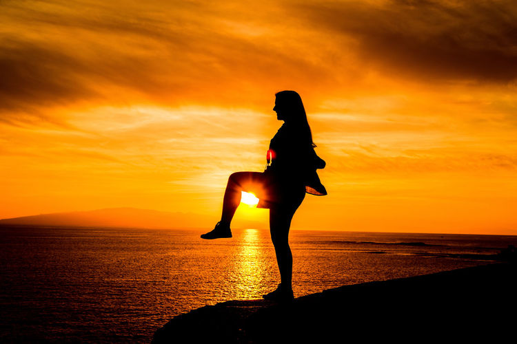 Silhouette woman standing on one leg against sea during sunset