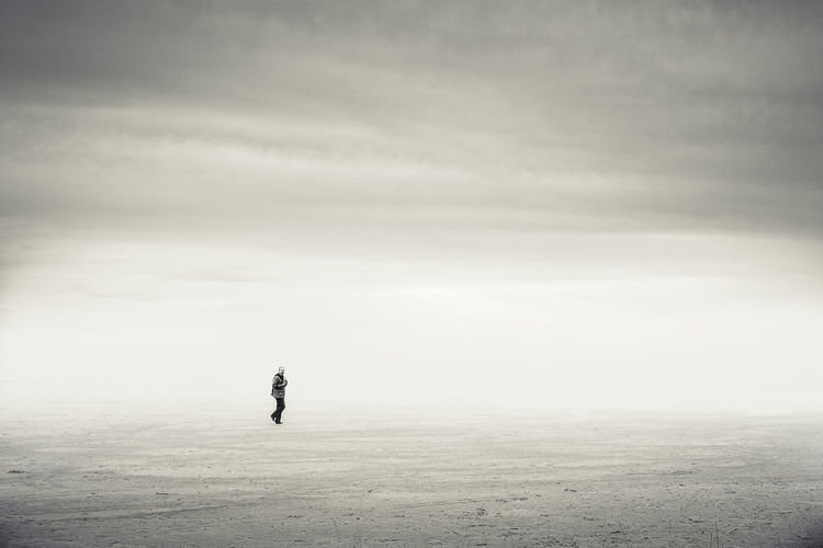Man walking on beach at ebro delta during foggy weather