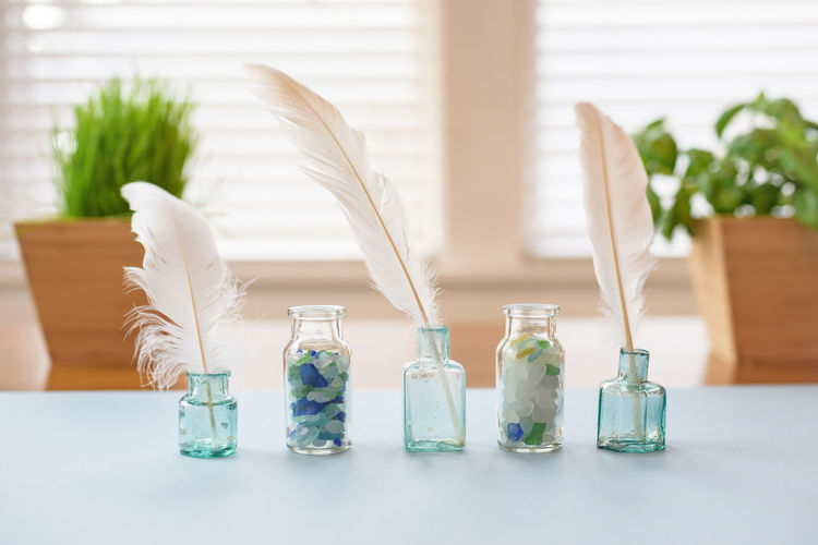 Close-Up Of Feather In Glass Bottles On Table