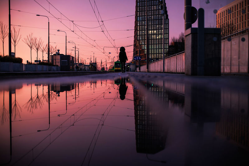 Reflection Of Person On Puddle In City During Sunset