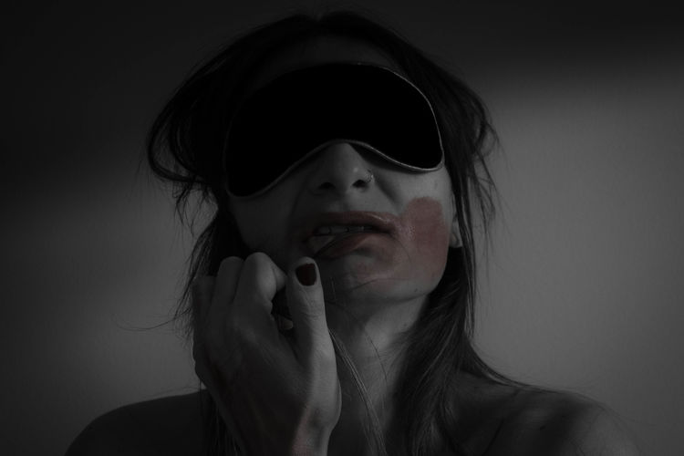 Close-up of naked woman wearing sleep mask with smudged lipstick against gray background