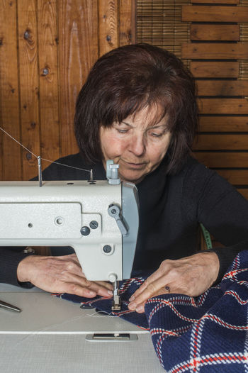 Senior Woman Sewing Textile On Machine