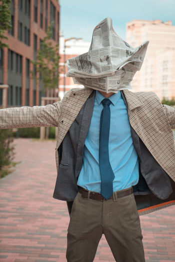 Businessman with newspaper on face standing with arms outstretched in city