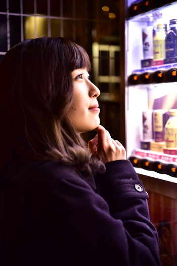 Side view of teenage girl looking away at store