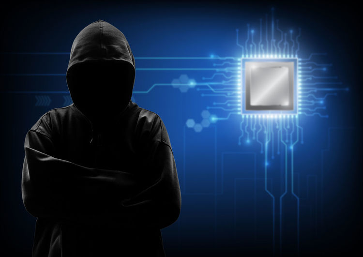 Computer hacker in hooded shirt standing against interface