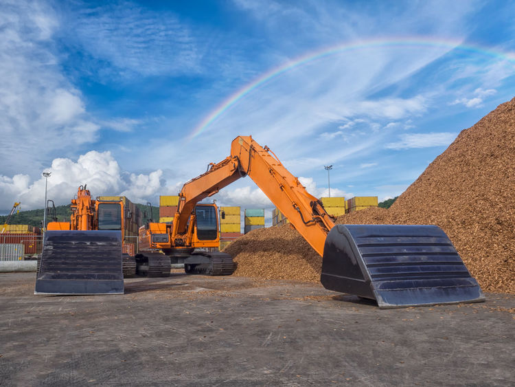 Woodchips storage in yard and backhoe for handling. Backhoe Built Structure Chip Cloud - Sky Construction Machinery Construction Site Day Development Digging Discharged Earth Mover Heap Industry Load Machinery No People Outdoors Progress Sky Wooden Yard