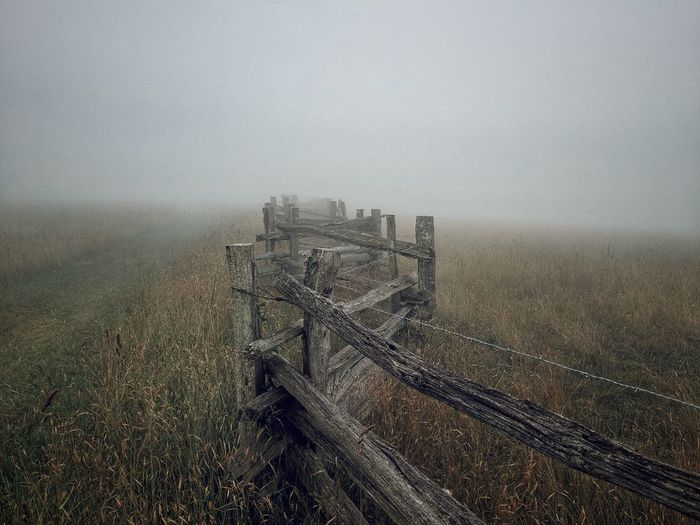 Fence on field against sky in fog