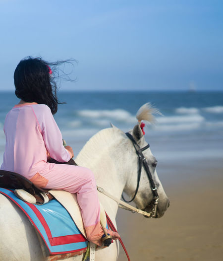 Rear view of girl riding horse in sea