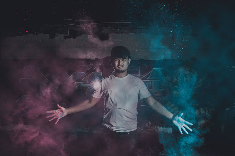 Digital composite image of man standing amidst powder paint at night