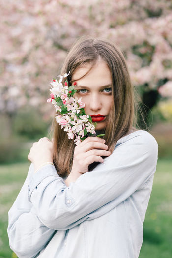 Portrait of beautiful woman standing by flowering plant