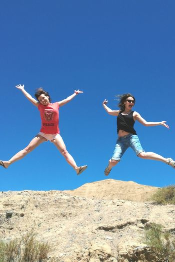 Low angle view of young woman jumping against clear blue sky
