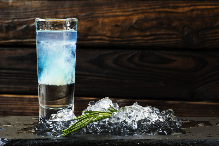 Close-up of cocktail served with ice cubes on slate