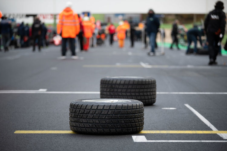 Close-up of tires with people in background