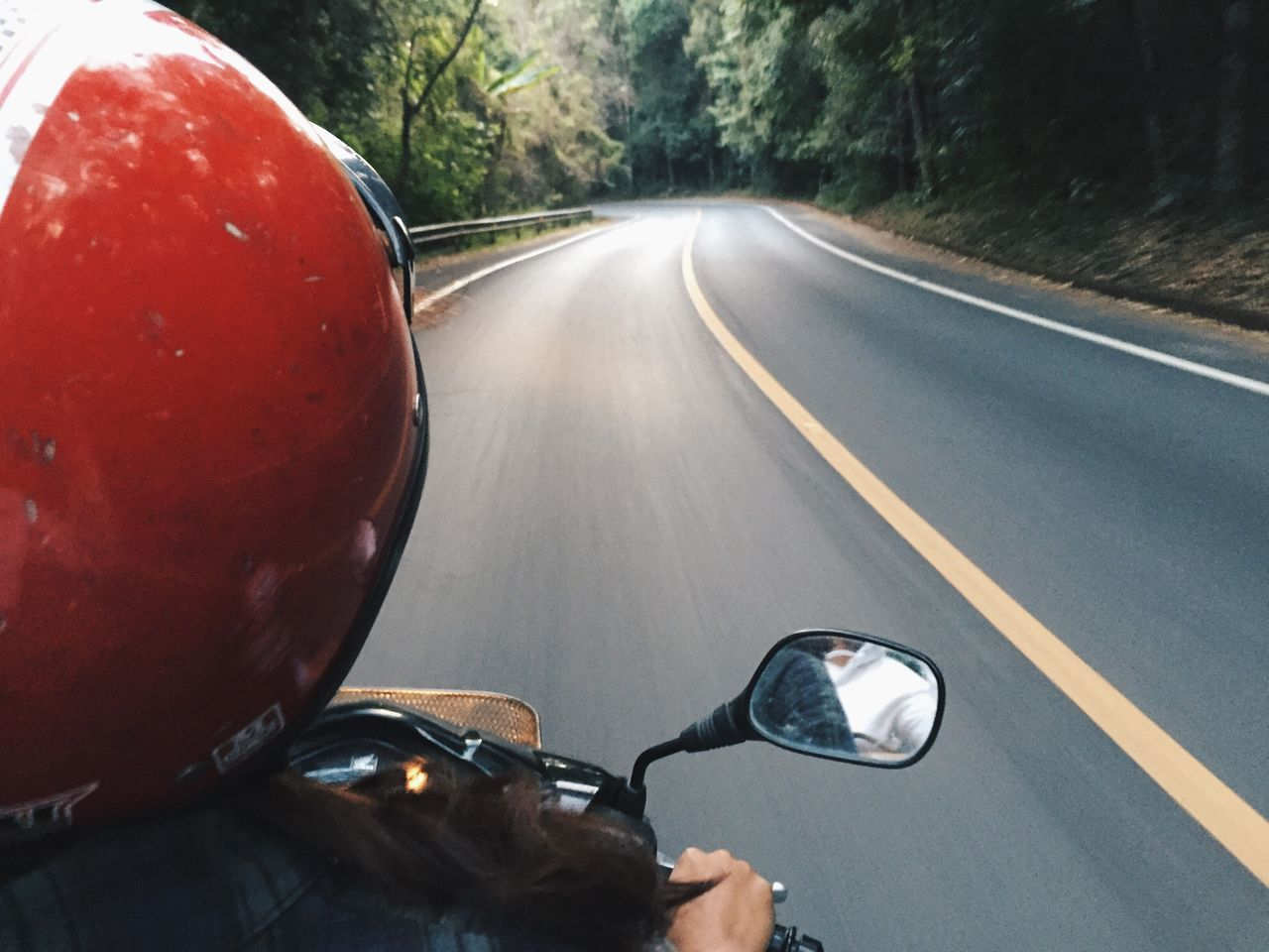 Rear view of woman riding scooter