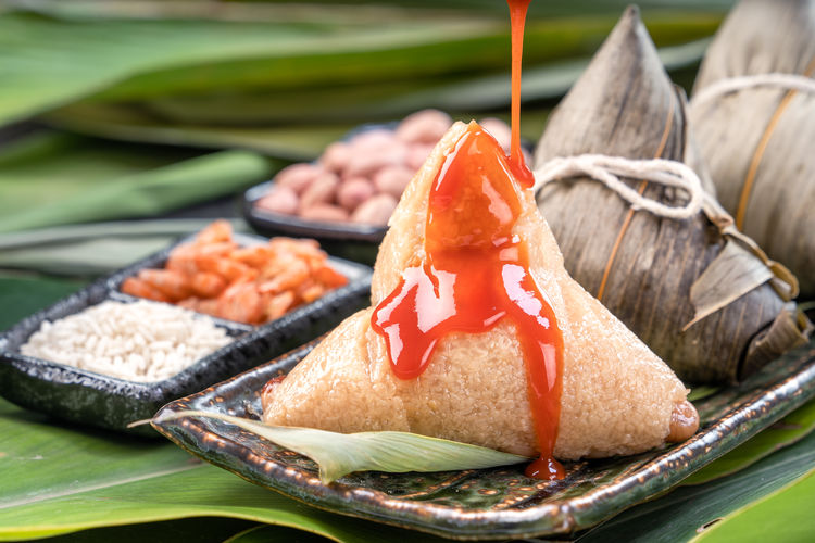 Zongzi Rice Dumpling  Duanwu Taiwan Dragon Boat Festival Chili  Sauce Tomato Ketchup Sweet Filling Stuff Ingredient Lifestyle Eating Table Chinese Food Green Background Gourmet Chopsticks Cuisine Bamboo Leaf Wrapped Meal Fresh Tamale Cooked Holiday Event Tradition Traditional ASIA Delicious Recipe Delicacy Closeup Copyspace Glutinous Sticky Peanut Dried Shrimp Plate Summer