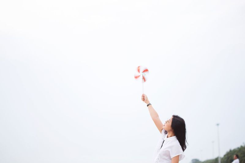 Low angle view of woman holding balloons against clear sky