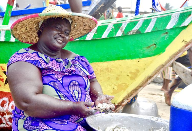 Overweight smiling woman selling seafood at beach