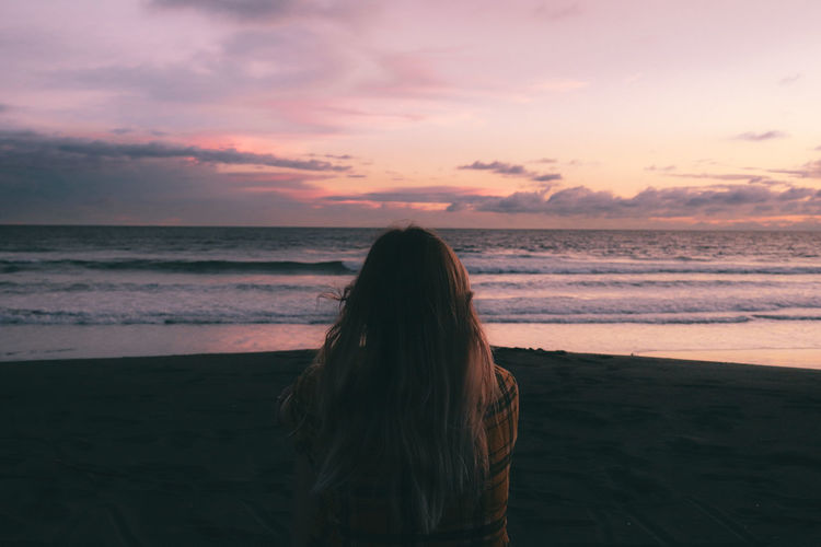 Girl sitting and watching the sunset