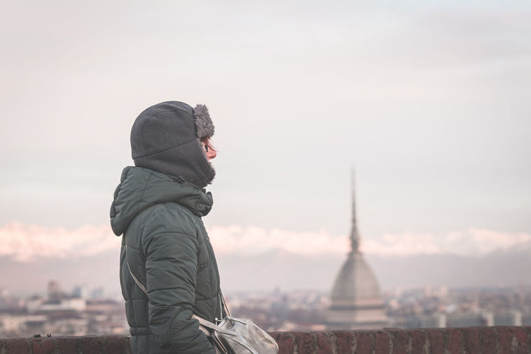 Tourist looking at panoramic view of Torino (Turin, Italy) from balcony above. Winter time, snowcapped Alps in the background. Selective focus, vintage style, toned image. Close-up Cold Temperature Day Focus On Foreground Knit Hat Leisure Activity Nature One Person Outdoors People Real People Sky Sunset Warm Clothing Winter Women
