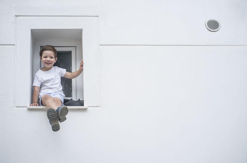 Full length portrait of smiling boy sitting at window
