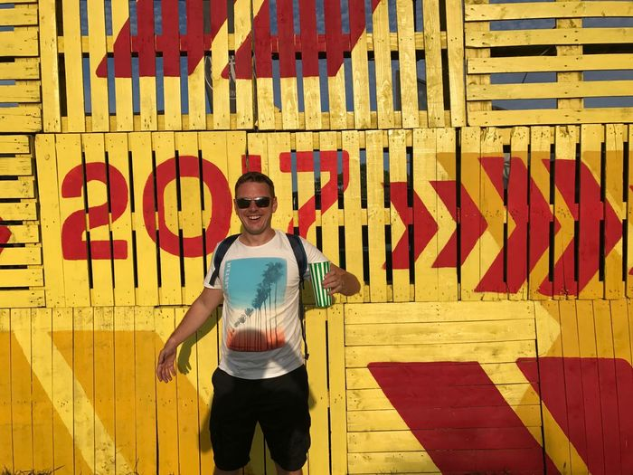 Portrait of smiling mid adult man holding drink while standing against yellow wall