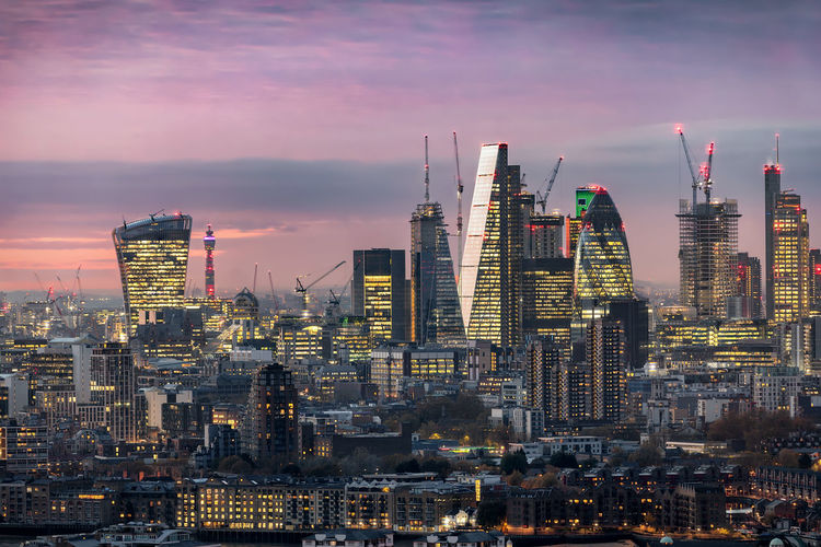 The illuminated City of London just after sunset Center City Of London Financial District  Lights London Modern Skyscrapers United Kingdom Architecture Bank Built Structure City Cityscape Evening Illuminated Modern Money Sky Skyscraper Stock Market Sunset Tall Tower Travel Destinations Urban Skyline