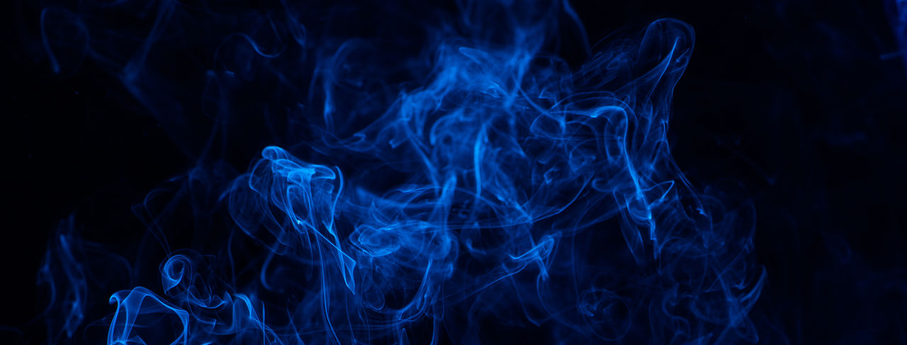 Conceptual image of blue color smoke isolated on dark black background, halloween concept design