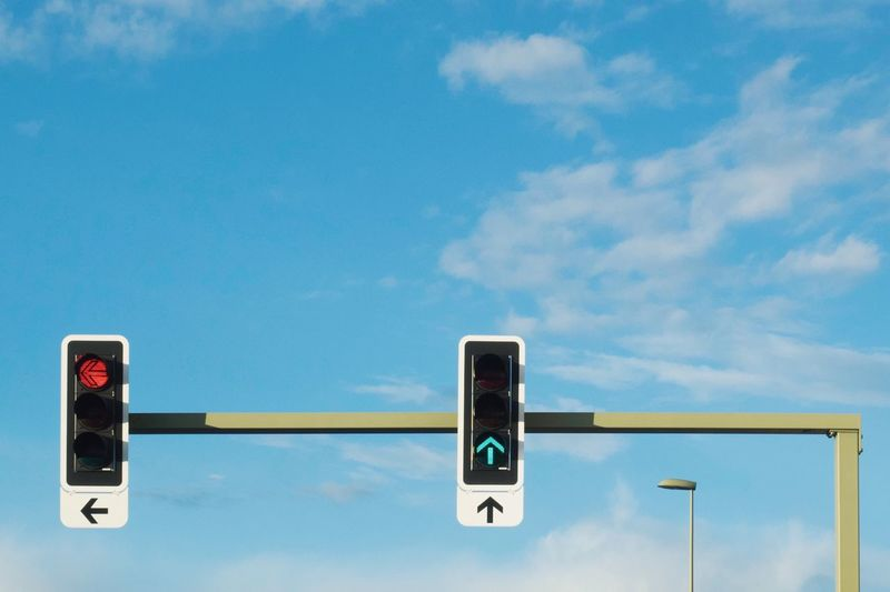 Low angle view of road signals against blue sky