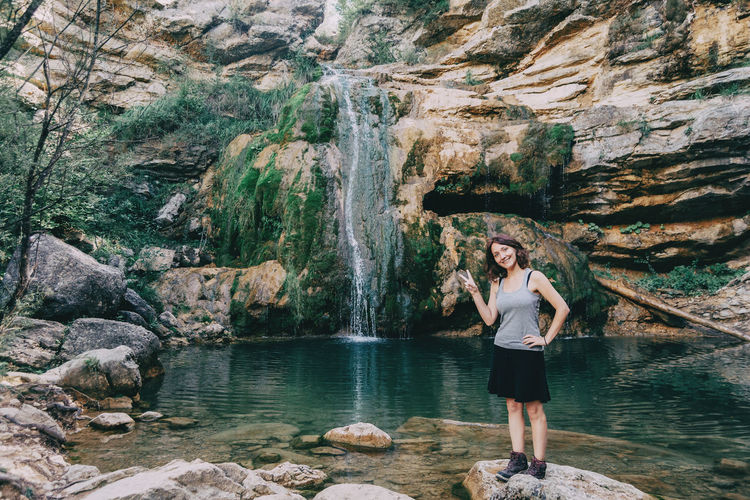 Woman next to a waterfall looking at camera