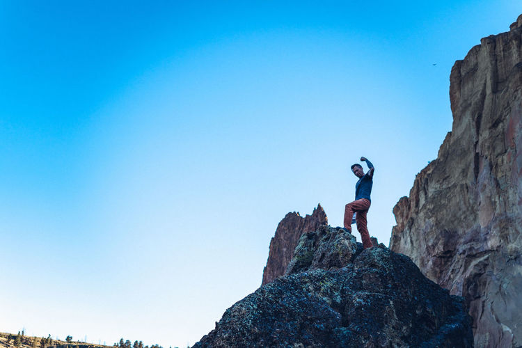 Man standing on rock against clear blue sky