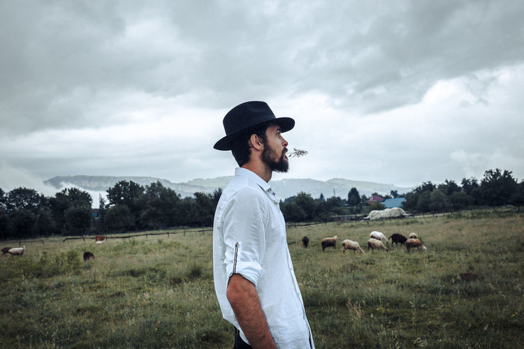 A handsome young man. Photo on nature. The guy wears a beard and medium length hair. He has an attractive face and a slim body. The man wears a black hat, a white shirt and trousers. Photo taken with daylight on a cloudy day in a mountainous area in the Caucasus. Green meadows and sky with clouds in the background. Freedom Hat Natural Animal Themes Casual Clothing Cloud - Sky Countryside Domestic Animals Field Grass Hat Land Leisure Activity Lifestyles Male Nature One Person Plant Portrait Real People Side View Sky Standing Young Adult Young Men
