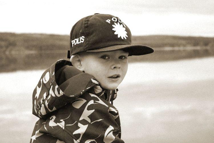 Close-up portrait of boy wearing cap against river