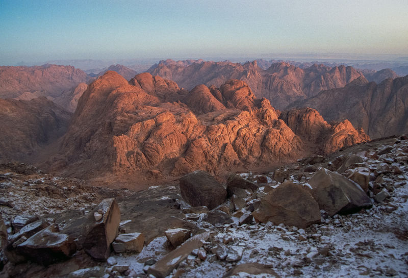 A dusting of desert snow covers the cold desolate top of Mt Sinai as one looks across the red-granite mountain peaks on the Sinai Peninsula. Also known by the names Mount Horeb and Gabal Musa (the 'Mountain of Moses'), the mountain is considered to be a the likely location of the biblical Mount Sinai. Mount Sinai is mentioned many times both the Bible, and the Quran, particularly in the book of Exodus. According to Jewish, Christian, and Islamic tradition, the biblical Mount Sinai was the place where Moses received the Ten Commandments. Mt Sinai sits at 2,285 m (7,497 ft) in the St Katherine region of the Sinai Peninsula, Egypt. Shot taken on film. Love Life, Love Photograph Beauty In Nature Canyon Commandments Desert Egypt Exodus Gabal Musa Granite Landscape Moses Mount Horeb Mountain Mountain Of Moses Nature Nature Red Redhead Rock Rock - Object Sinai Sinai Peninsula Sky Snow Sunset Valley