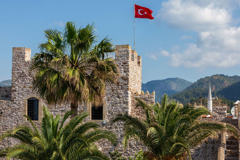 Kalesi Marmaris Castle , Marmaris , Turkey Castle Kalesi Marmaris Castle Museum National Flag Of Turky Turkey Architecture Beauty In Nature Building Building Exterior Built Structure City Day Flag Green Color Growth Marmaris Marmaris Castle Mountain National Flag Nature No People Outdoors Palm Tree Plant Sky Travel Destinations Tree Tropical Climate