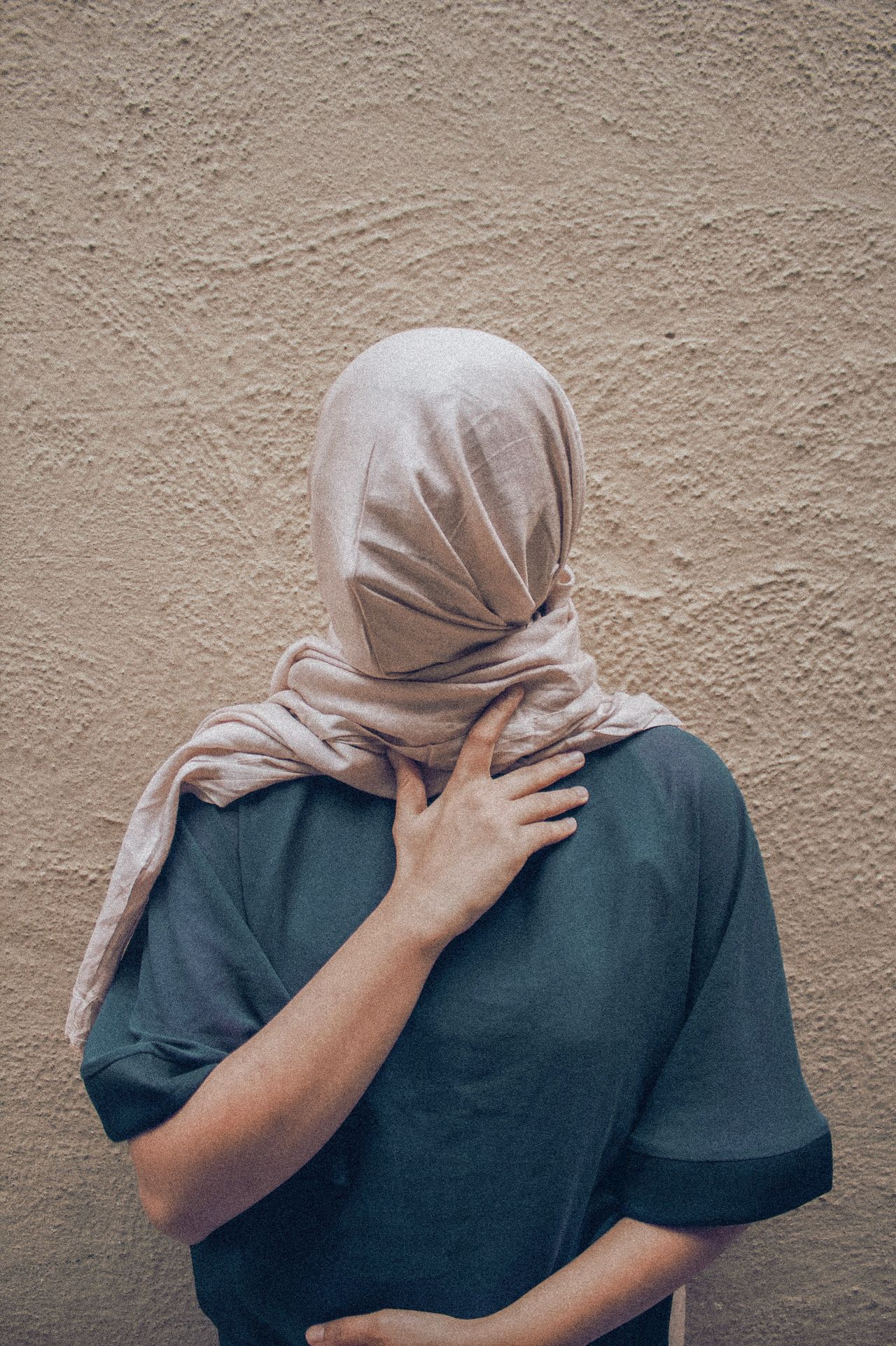 Woman covering face with scarf against wall