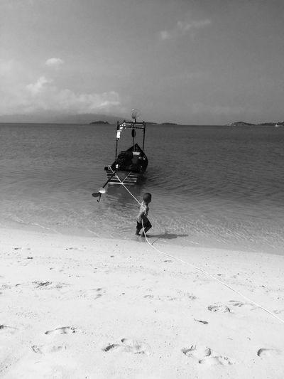 Boy mooring boat at beach against sky