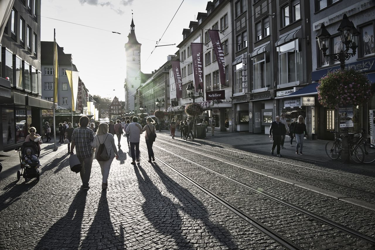 architecture, city, group of people, building exterior, real people, railroad track, built structure, track, transportation, rail transportation, large group of people, crowd, men, street, mode of transportation, women, travel, city life, walking, lifestyles