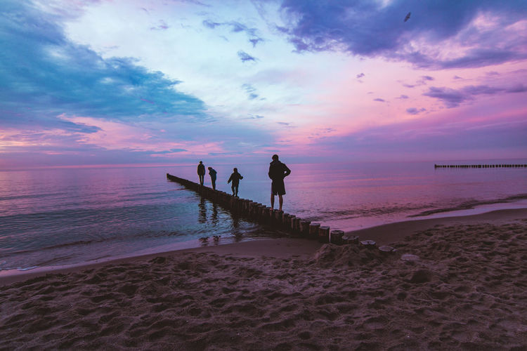 Sky Water Beach Sea Cloud - Sky Real People Sunset Beauty In Nature Land Scenics - Nature Horizon Over Water Horizon Tranquility Lifestyles Tranquil Scene Leisure Activity Men Nature Women Outdoors