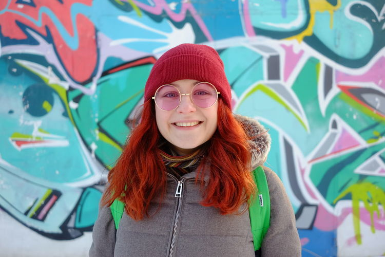 young ginger girl looks to a camera over graffiti wall Portrait Smiling Cheerful Looking At Camera Confidence  Headshot Pink Hair Redhead Front View Street Art Hip Hop Mural Medium-length Hair Aerosol Can Spray Paint Graffiti Fresco Breakdancing Scribble Paint Can Dyed Hair Handstand  Paint Roller Week Spraying Holi Bling Bling
