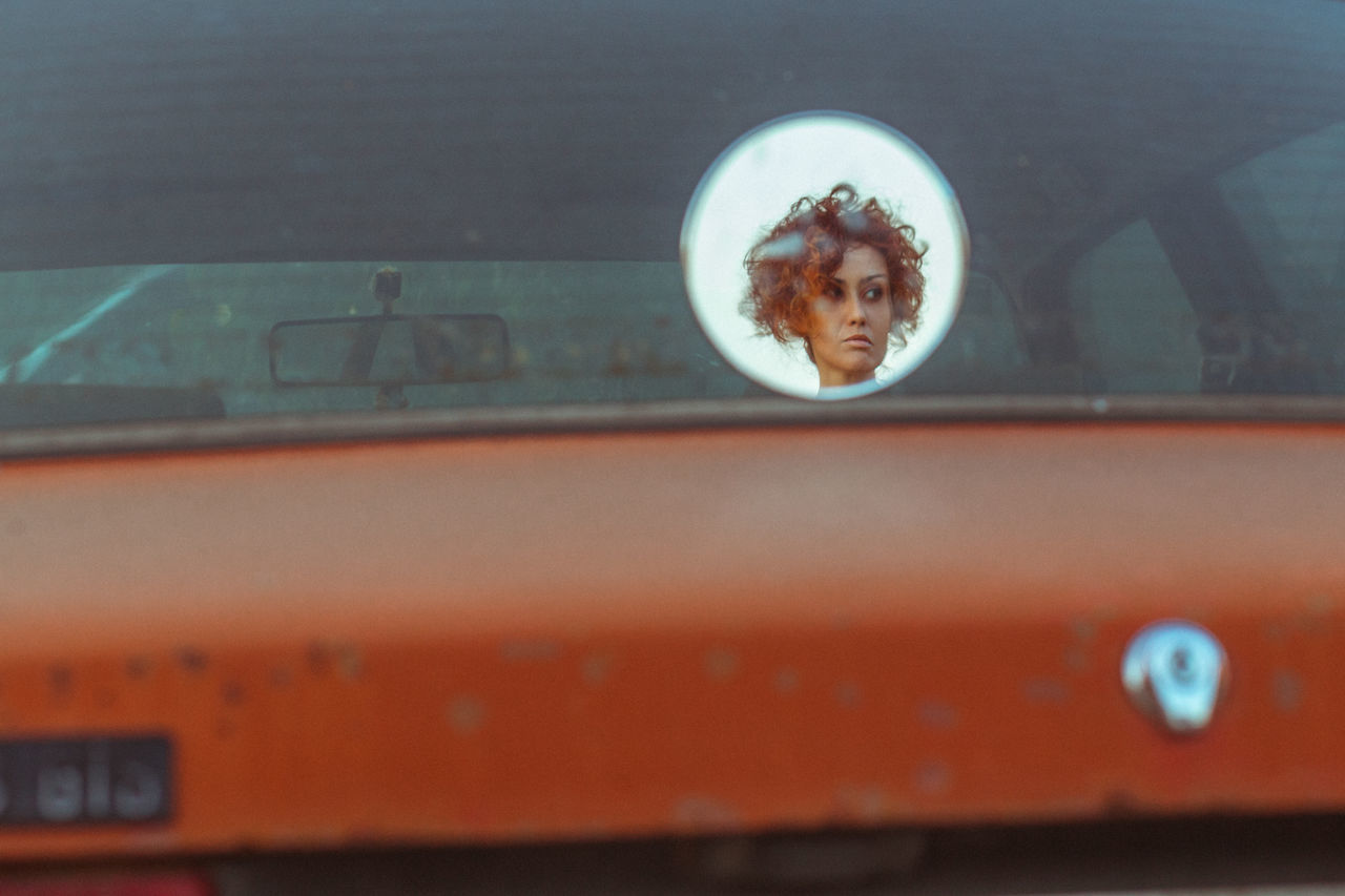 Woman reflecting on rear windshield of car