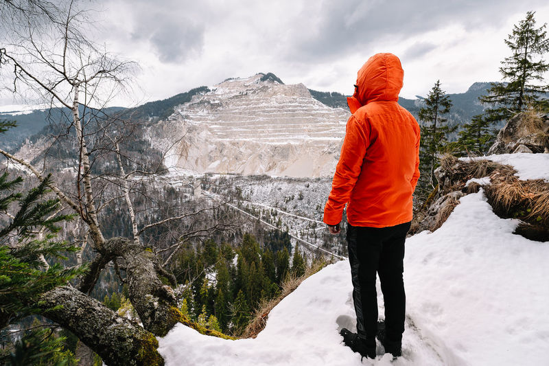 Rear view of person in orange jacket standing on snowcapped mountain during winter