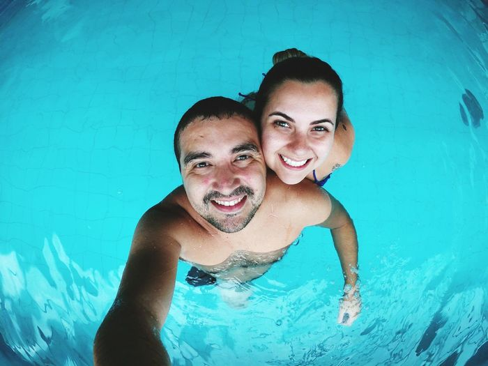 Portrait of smiling couple swimming in pool